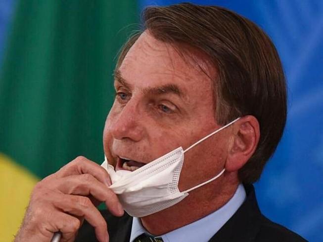 Tổng thống Brazil Jair Bolsonaro tháo khẩu trang tại một cuộc họp báo về COVID-19 vào tháng 3. Ảnh: Andre Borges/AP