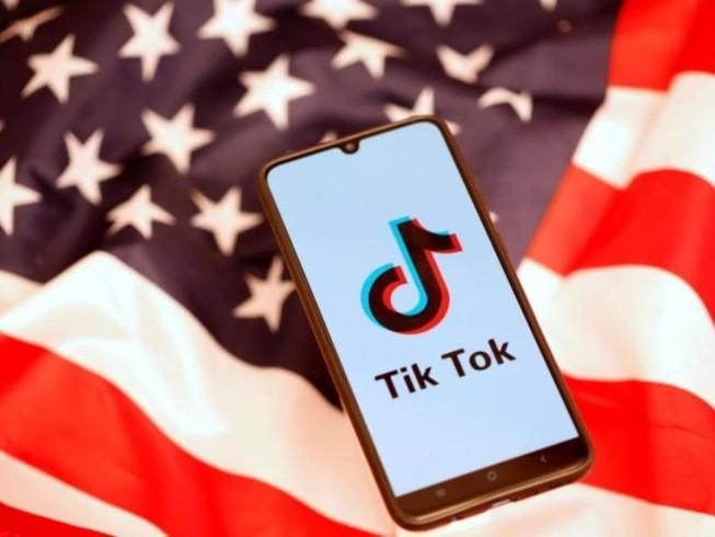 Điện thoại có logo của TikTok đặt trên lá cờ Mỹ. Ảnh:REUTERS/Dado Ruvic