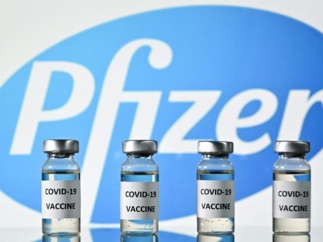 Những lọ vaccine ngừa COVID-19 đặc trước logo tập đoàn dược phẩm Pfizer.