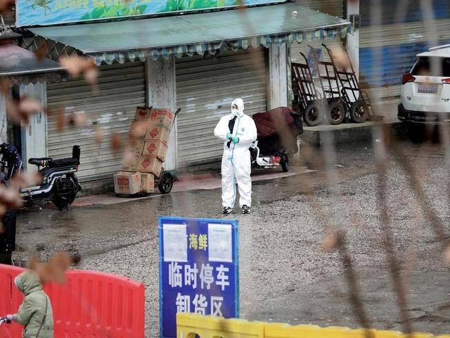 Một nhân viên y tế trong bộ đồ bảo hộ tại chợ hải sản ở Vũ Hán, Trung Quốc, vào ngày 10-1.