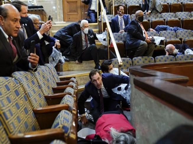 Thành viên Quốc hội Mỹ tìm cách trốn khi người biểu tình xông vào Điện Capitol. Ảnh: AP