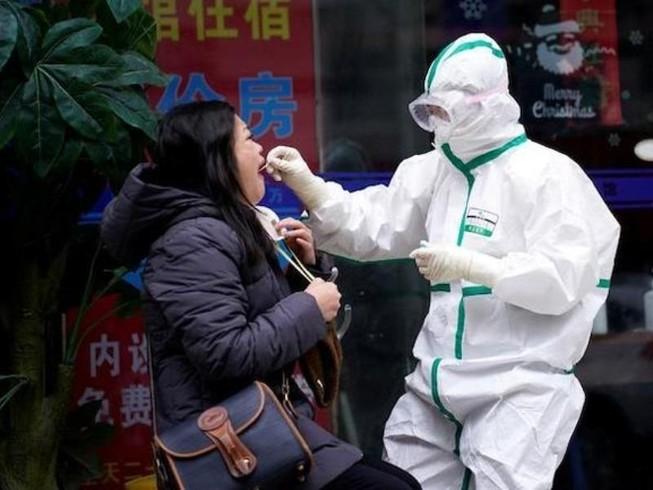 Một nhân viên y tế Trung Quốc đang lấy mẫu xét nghiệm từ một phụ nữ.