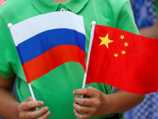 Một đứa trẻ cầm quốc kỳ của Nga và Trung Quốc tại lễ đón Tổng thống Nga Vladimir Putin đến thăm Bắc Kinh, ngày 25-6-2016.