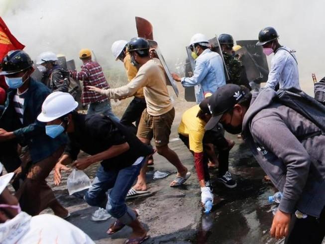 Người dân dùng khiên chắn chống lại hơi cay và vòi rồng do cảnh sát sử dụng trong cuộc biểu tình ở Naypyitaw, Myanmar, ngày 8-3.