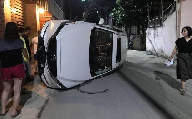 Xe hơi đâm gãy cột điện rồi lật nghiêng giữa đường