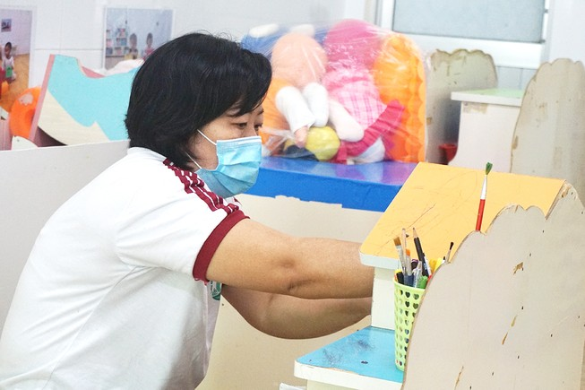 Giáo viên Trường Mầm non Hạnh Thông Tây, quận Gò Vấp vệ sinh trường lớp để đón trẻ đi học lại. Ảnh: NGUYỄN QUYÊN