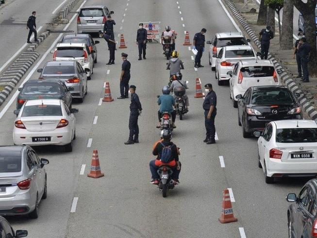 Cảnh sát kiểm soát đi lại người dân trên đường phố thủ đô Kuala Lumpur (Malaysia). Ảnh: AP