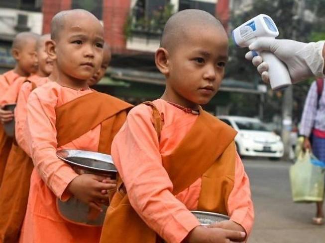 Các chú tiểu được kiểm tra nhiệt độ trên đường phố Yangon (Myanmar). Ảnh: AFP