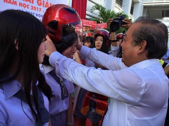 Phó Thủ tướng Trương Hòa Bình đội mũ bảo hiểm cho HS