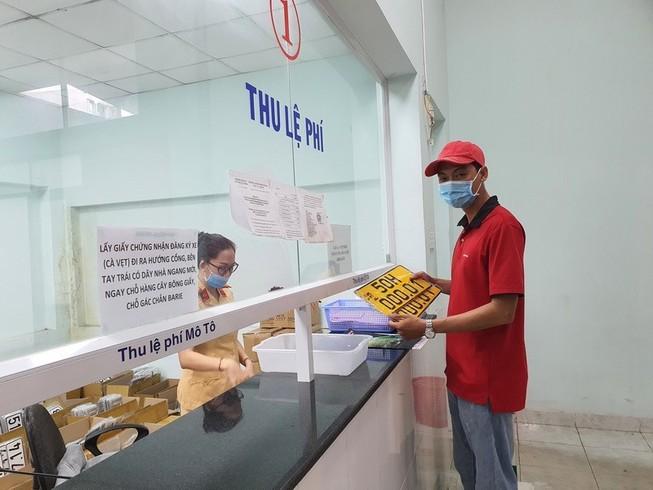 Người dân đổi biển số nền màu vàng tại TP.HCM. Ảnh: T.NHUNG