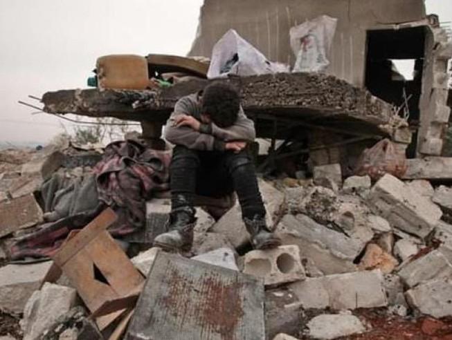Một cậu bé Syria ngồi khóc ở làng Kafr Taal, tỉnh Aleppo, Syria.