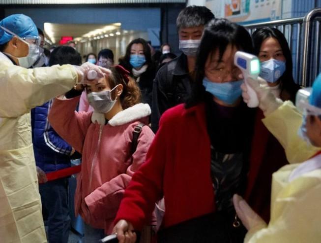 Nhân viên y tế kiểm tra thân nhiệt hành khách đi tàu ở Trung Quốc.