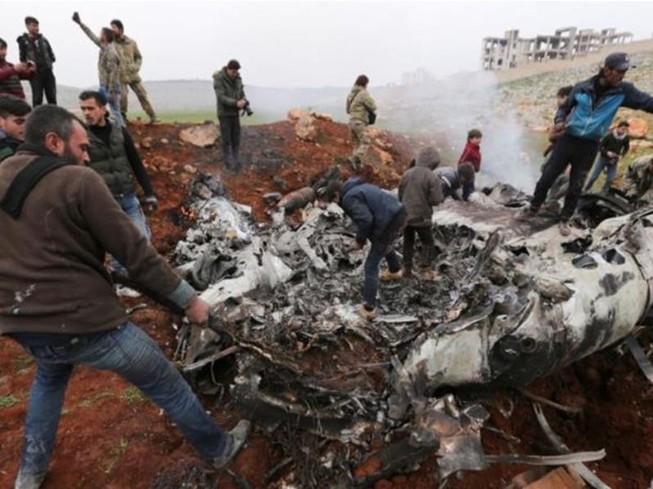 Người dân tập trung quanh mảnh vỡ chiếc trực thăng của chính phủ Syria bị bắn rơi ở tây Aleppo, Syria. Ảnh: AP