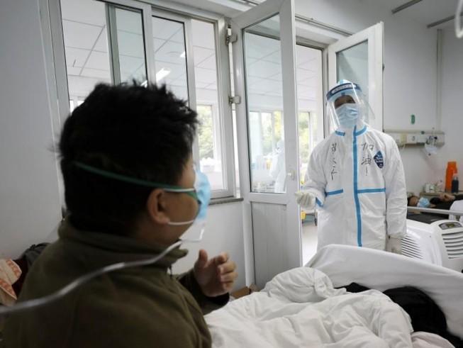 Một nhân viên y tế trong trang phục bảo hộ tương tác với một bệnh nhân trong khu cách ly tại bệnh viện Jinyintan ở Vũ Hán, Trung Quốc.