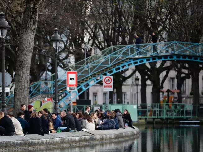 Người dân tập trung tại các bờ kênh đào Saint-Martin ở Paris (Pháp) hôm 25-3 khi các nhà hàng, tiệm cà phê đóng cửa do dịch COVID-19. Ảnh: AFP