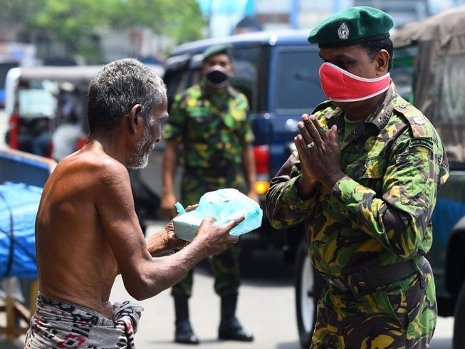 Cảnh sát Sri Landa cung cấp thức ăn cho người vô gia cư giữa lúc nước này phát lệnh giới nghiêm toàn quốc ngăn COVID-19. Ảnh: AFP