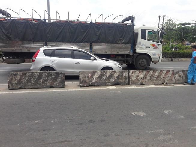 Xe tải ép ô tô vào dải phân cách ở Bình Tân