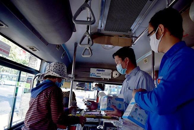 Phát khẩu trang và nước rửa tay miễn phí cho người đi xe buýt