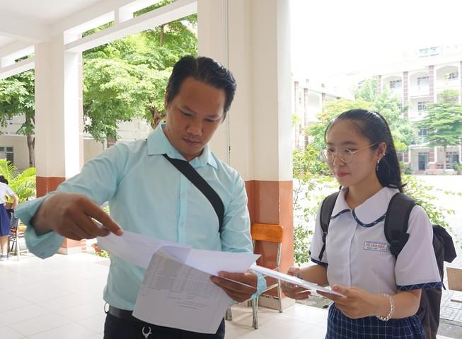 Giám thị kiểm tra giấy tờ của thí sinh trước khi vào phòng thi. Ảnh: NQ