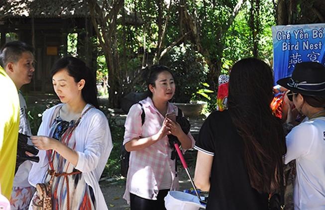 Một nữ HDV người Trung Quốc (mặc áo ca rô) đang giới thiệu cho một đoàn khách nước này tại một điểm du lịch ở Nha Trang. Ảnh minh họa: TẤN LỘC