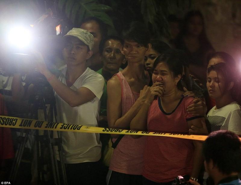 Một phụ nữ người Philippines bật khóc khi thấy xác của chồng mình bên cạnh một tấm biển có ghi 'Tôi là kẻ bán ma túy.