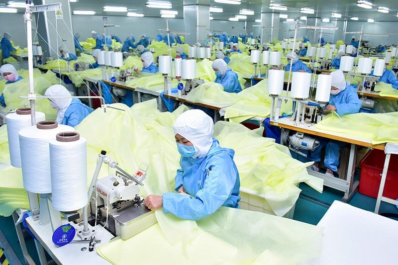 Công nhân mang khẩu trang tăng ca ở Hồ Bắc (Trung Quốc). Ảnh: CHINA DAILY