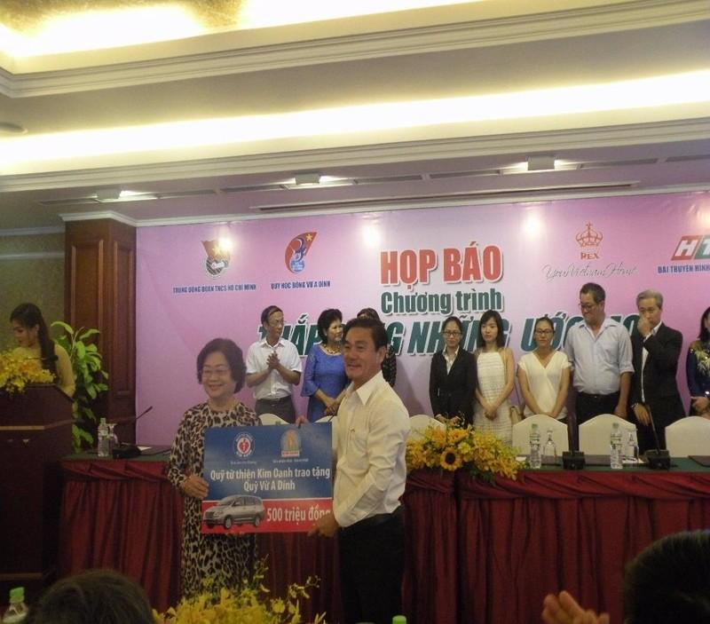 Bà Trương Mỹ Hoa, đại diện Qũy nhận quà tặng tượng trưng từ Qũy từ thiện Kim Oanh.