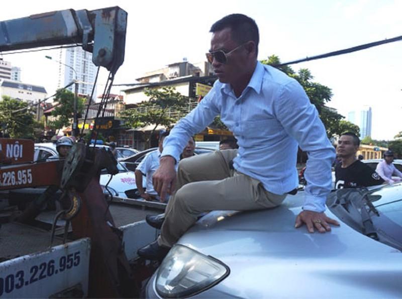 Tài xế 'cố thủ' trên nắp capo khi xe bị cẩu đi - ảnh 1