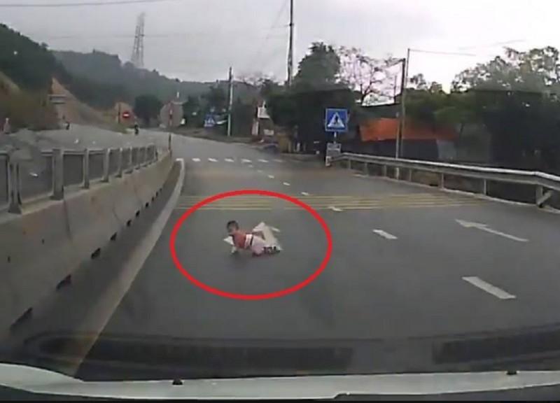 Kinh hãi cháu bé bò qua đường trước đầu ô tô - ảnh 1