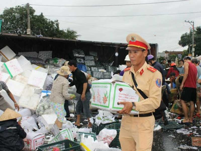 Xe tải lật, CSGT cùng dân giúp gom hàng - ảnh 1