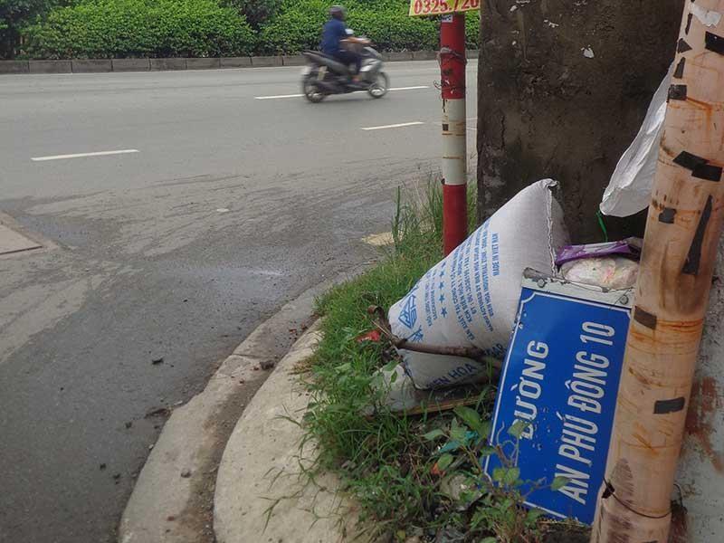 Bảng tên đường, biển báo giao thông nằm dưới đường - ảnh 1