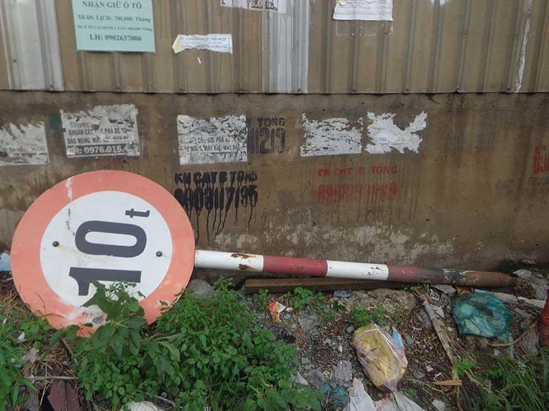 Bảng tên đường, biển báo giao thông nằm dưới đường - ảnh 2