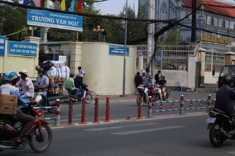 Vô tư băng qua đường mặc hàng rào chắn - ảnh 1