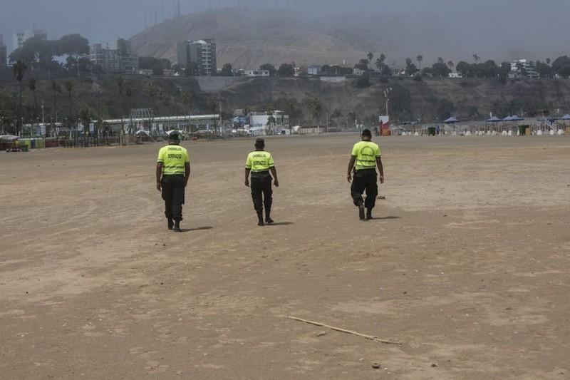 Những nhân viên an ninh ngày 24-3 chỉ còn đi tuần tra trên một bãi biển không một bóng người. Ảnh: AP 2