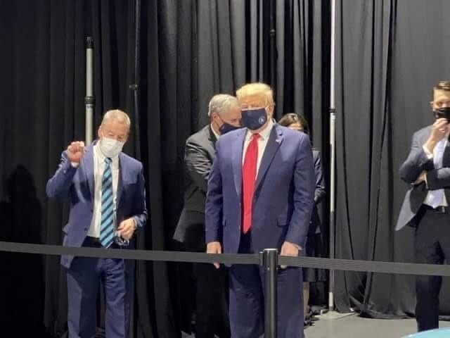 Tổng thống Mỹ Donald Trump đầu chuyến thăm nhà máy Ford ở TP Ypsilanti, bang Michigan, Mỹ hôm 21-5 nhưng sau đó đã tháo ra. Ảnh: TWITTER (trước), AFP (sau) 1