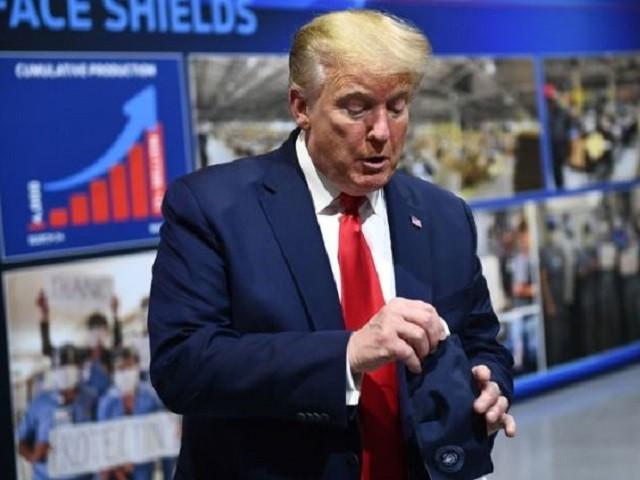 Tổng thống Mỹ Donald Trump đầu chuyến thăm nhà máy Ford ở TP Ypsilanti, bang Michigan, Mỹ hôm 21-5 nhưng sau đó đã tháo ra. Ảnh: TWITTER (trước), AFP (sau) 2