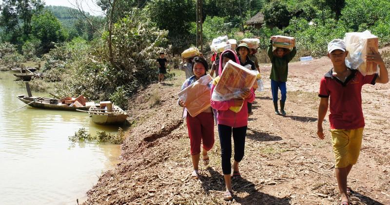 Người dân xã Phương Mỹ (huyện Hương Khê, Hà Tĩnh) đang bị lũ chia cắt phải đi đò rồi lội bộ nhiều km ra gần đường mòn Hồ Chí Minh nhận mì tôm và lương khô. Ảnh: Đ.LAM