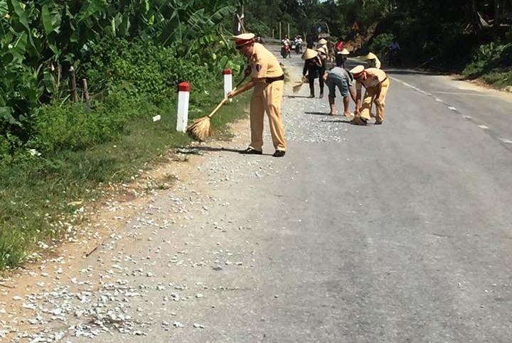 CSGT giúp dân nhặt tôm, quét đá dăm trên đường  - ảnh 1
