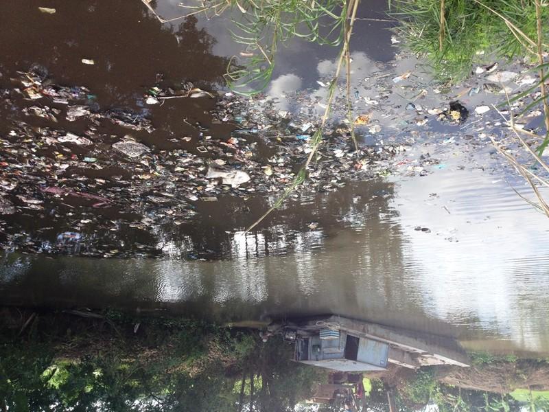 Nước kênh đen ngòm và đầy rác thải (ảnh KHÁNH HOÀNG)