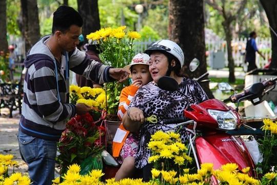 Giá hoa giảm sâu, nhiều khách đi bát phố cũng ghé vào hỏi mua. Một khách hàng tên Nga hào hứng chia sẻ, thấy giá rẻ, hoa lại đẹp nên đang đi trên đường chị tạt vào mua hoa cúc về chưng Tết.