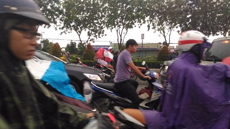 Mưa đổ xuống, người chạy xe máy ùn ùn dừng lại mặc áo mưa, ngay trong làn đường ô tô, và kẹt xe (đường Trường Chinh). Ảnh: Lâm Thông