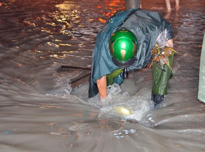 Một thượng sĩ công an đã đến cống thoát nước ven đường Đồng Khởi để móc rác, khơi thông dòng chảy.  Ảnh: zing