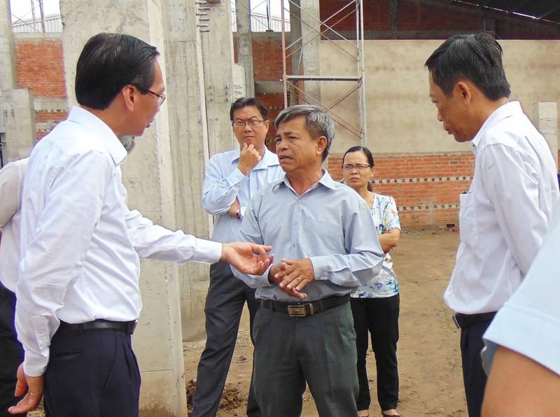 Ông Lê Thanh Liêm (bìa phải) đang trao đổi với đại diện Công ty CP Chế biến thực phẩm Hóc Môn. Ảnh: TRẦN NGỌC