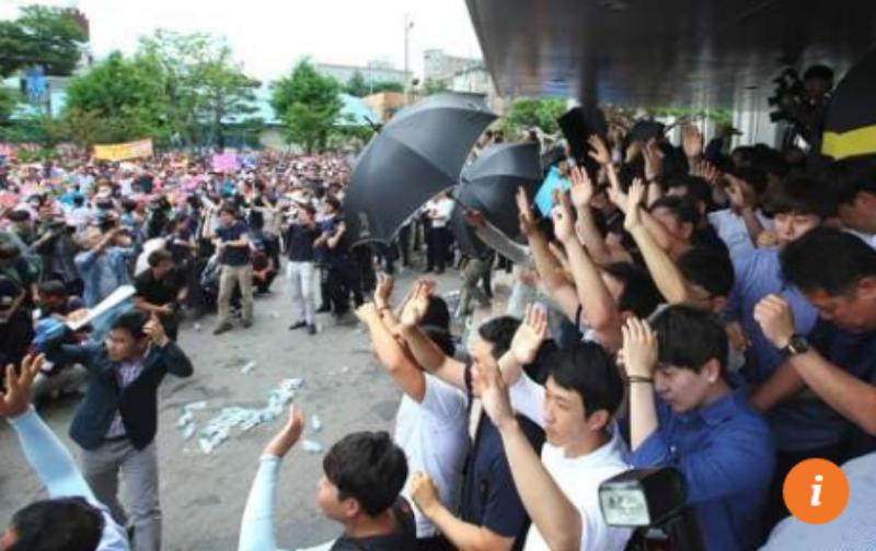 Bảo vệ dùng dù che chắn Thủ tướng Hwang Kyo-ahn khi bị ném trứng.