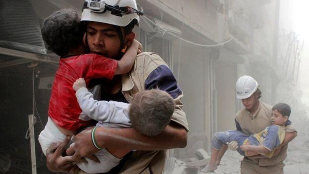 Nhân viên tổ chức White Helmets cứu người sau một trận không kích ở đông Aleppo (Syria).