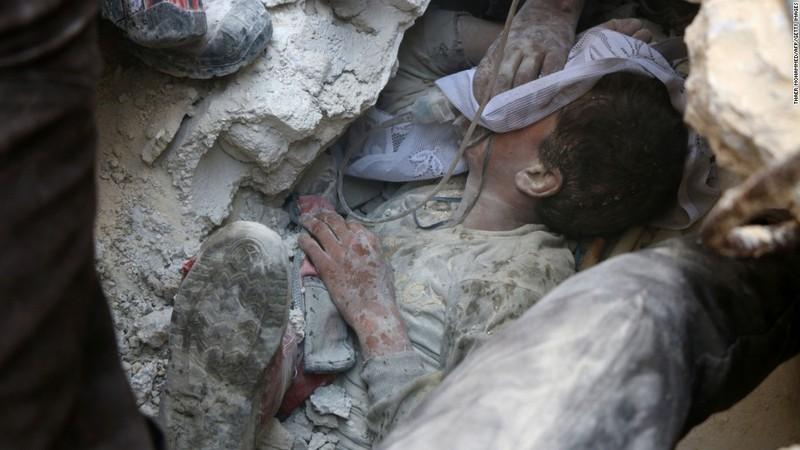 Jameel Mustafa Habboush, 13 tuổi, được cấp cứu sau khi bị đất đá chôn vùi do không kích.
