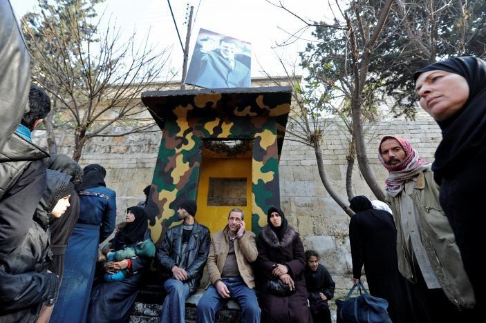 Người dân Aleppo đợi trước một trung tâm cảnh sát Syria để thăm người thân mới các khu vực phe nổi dậy kiểm soát ở đông Aleppo sơ tán sang, ngày 11-12. Ảnh: REUTERS