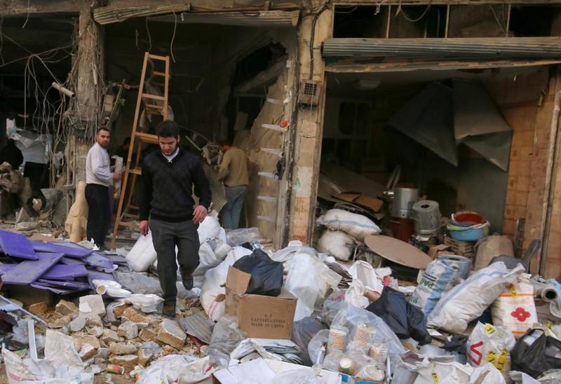 Người dân thu nhặt tài sản sau khi cửa hàng của mình ở quận al-Shaar (Aleppo) bị không kích trúng ngày 7-11.