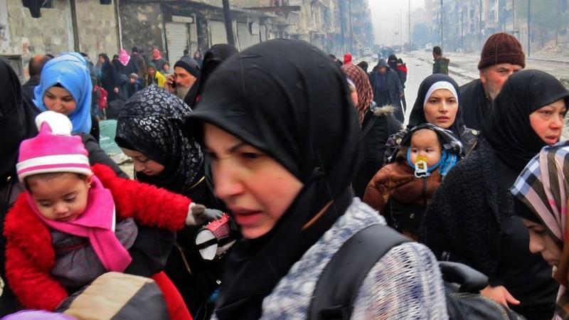 Người dân đến quận Fardo sau khi sơ tán khỏi quận Bustan al-Qasr (đông Aleppo) ngày 13-12. Ảnh: AFP