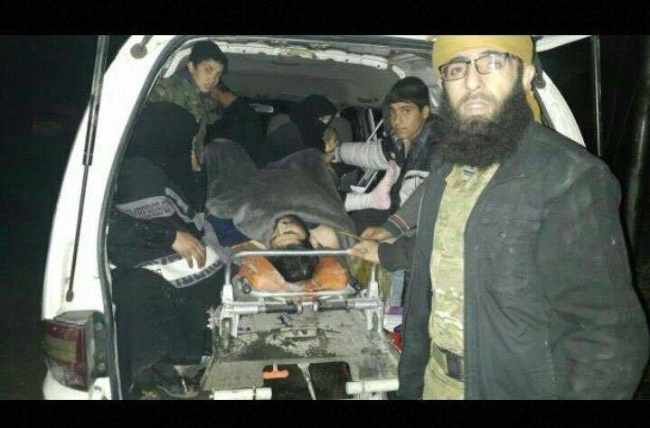 Tay súng nổi dậy và dân thường bị thương được đưa lên xe rời Aleppo. Ảnh: AMN